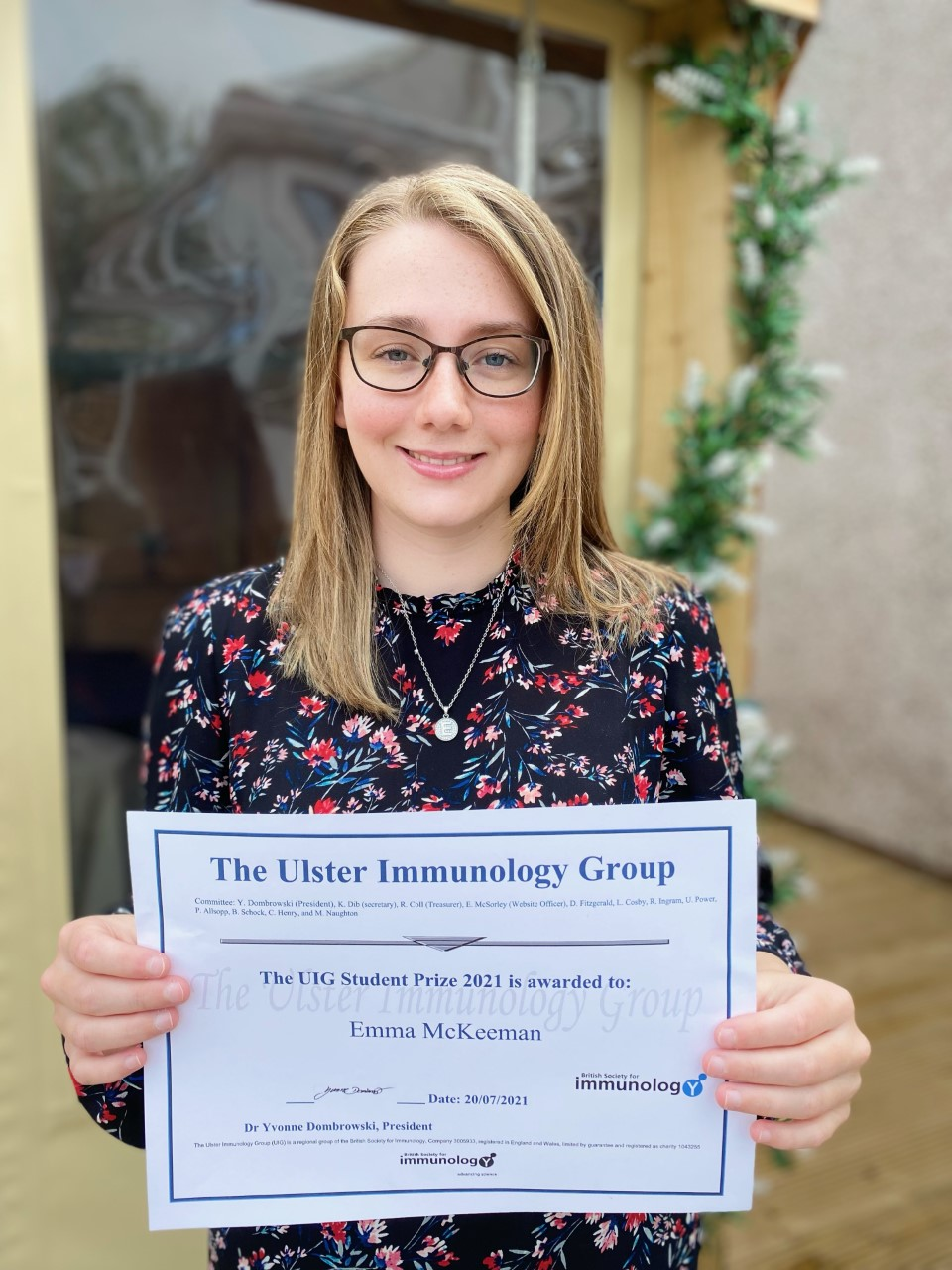 Woman with glasses holding a prize certificate