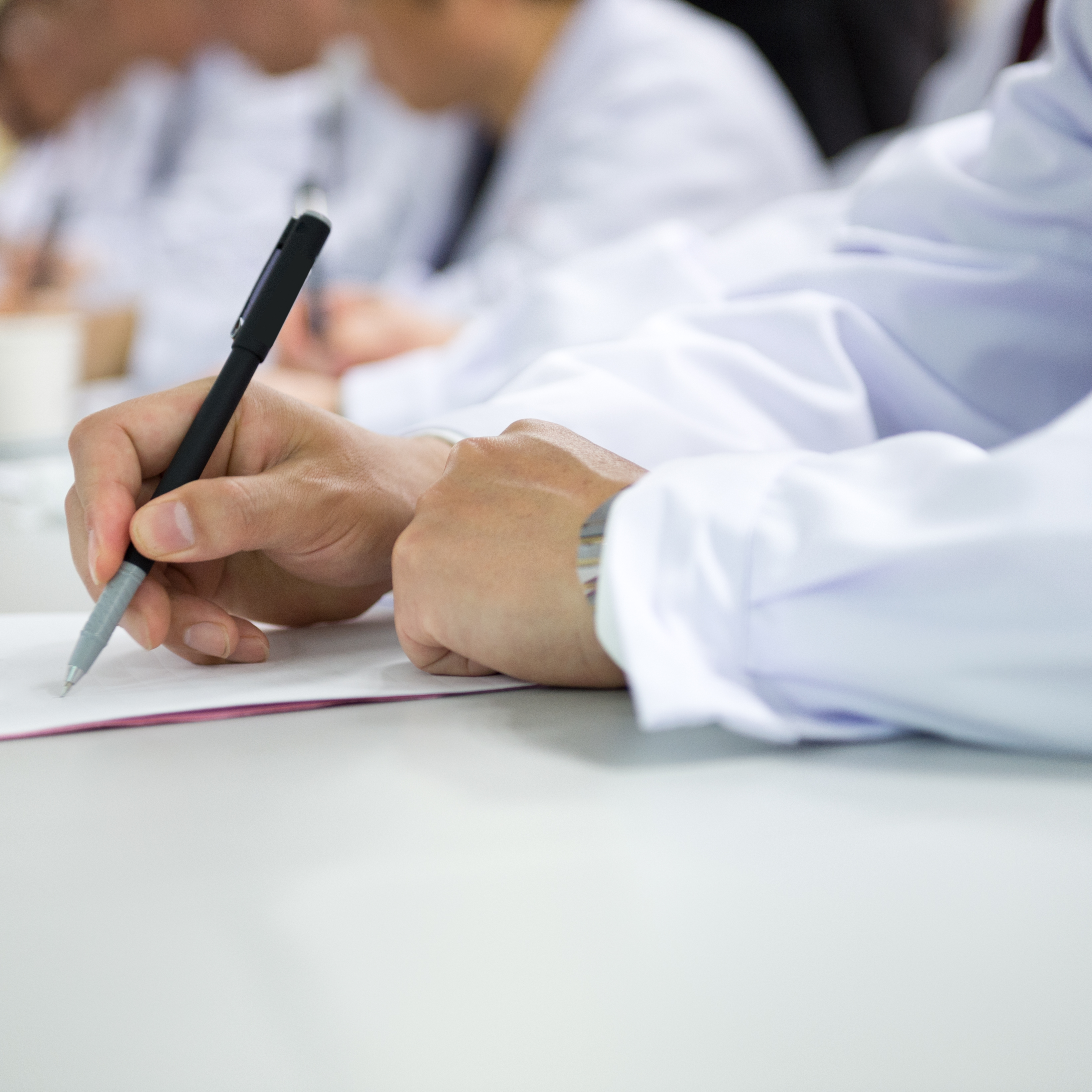 Doctors in labcoats writing at a conference